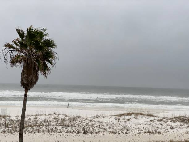 Pensacola Beach, FL, USA: Waves crashing on beach on overcast day in January stock photo