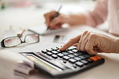 istock Pension calculation concept, old hands counting finances on a home calculator , close- up 1225117361
