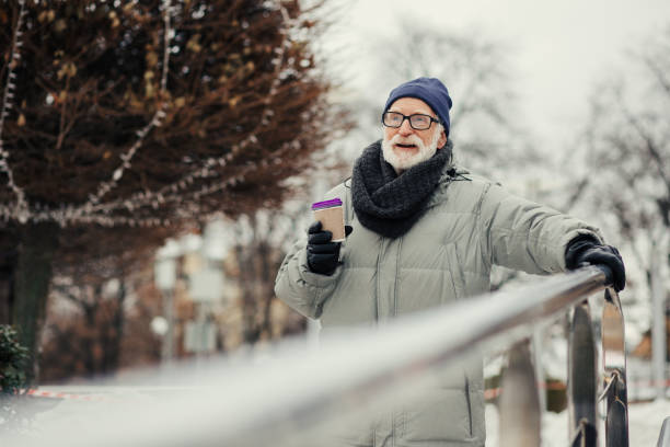 Pensioner in winter coat and black gloves putting hand on the handrail stock photo