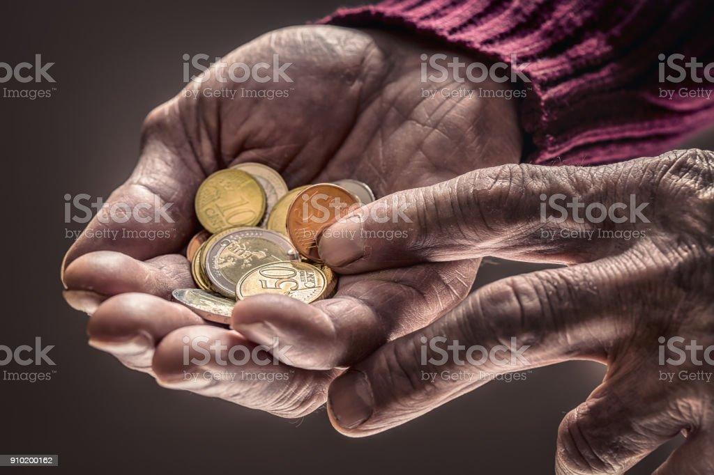 Rentner-Mann hält in Händen-Euro-Münzen. Thema der niedrigen Renten – Foto