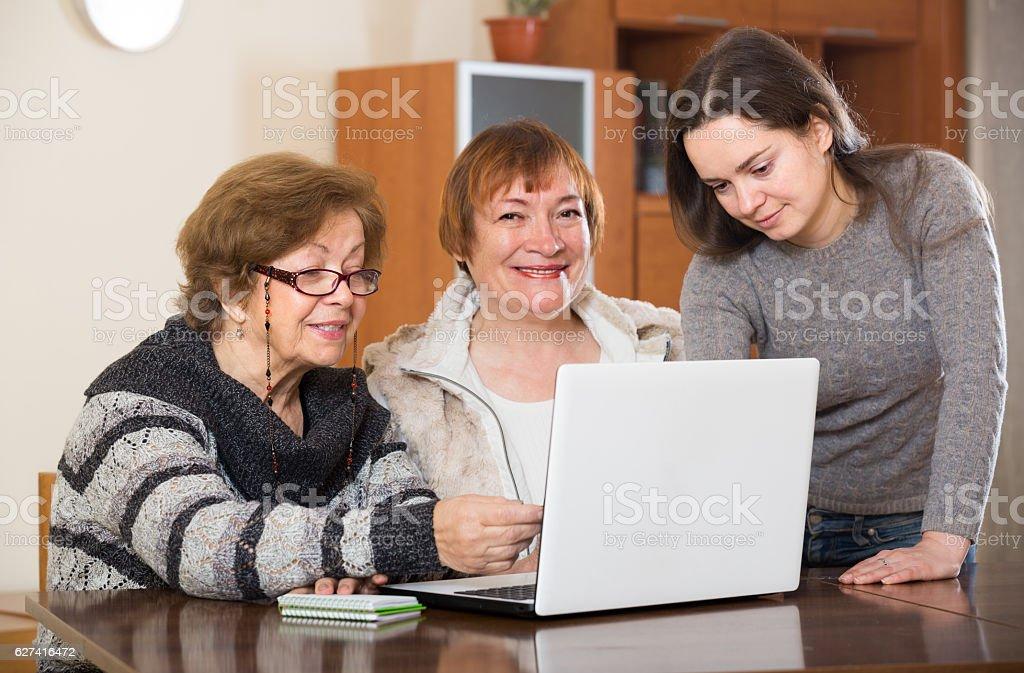 pensioners and relative with laptop stock photo