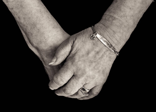 Pensioner's hands with medical alert bracelet for diabetes. Monochrome. stock photo