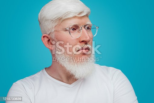 Crop tranquil albino bearded male in glasses and casual white shirt looking away and contemplating against blue background in studio