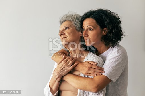 Pensive adult daughter hugging senior mother and looking away. Middle aged woman embracing elderly lady. Daughter affection concept
