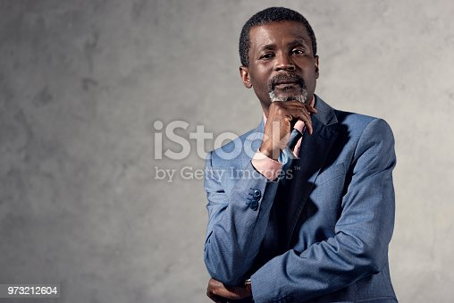 973213156 istock photo pensive african american businessman looking at camera 973212604