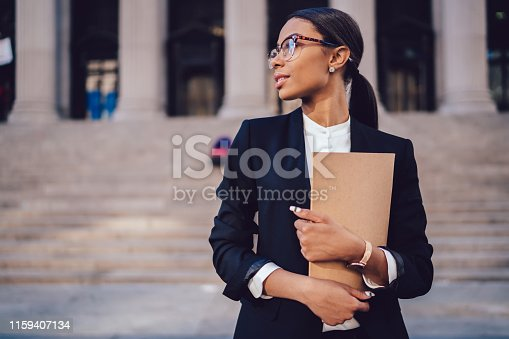 istock Pensive African American female lawyer in stylish formal suit holding folder with mock up area and looking away standing against courthouse. Half length of woman professional advocate with documents 1159407134