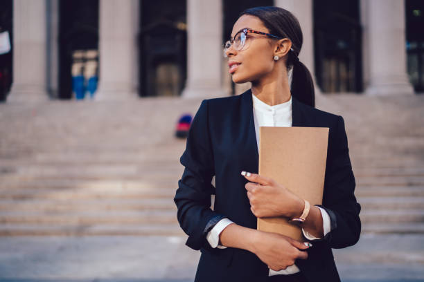 Pensive African American female lawyer in stylish formal suit holding folder with mock up area and looking away standing against courthouse. Half length of woman professional advocate with documents stock photo
