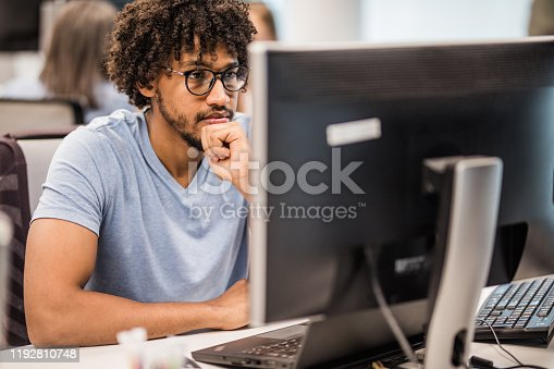 African American programmer brainstorming while working on desktop PC in the office.