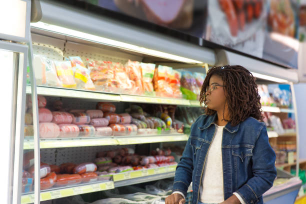 Pensive African American woman wheeling shopping cart stock photo