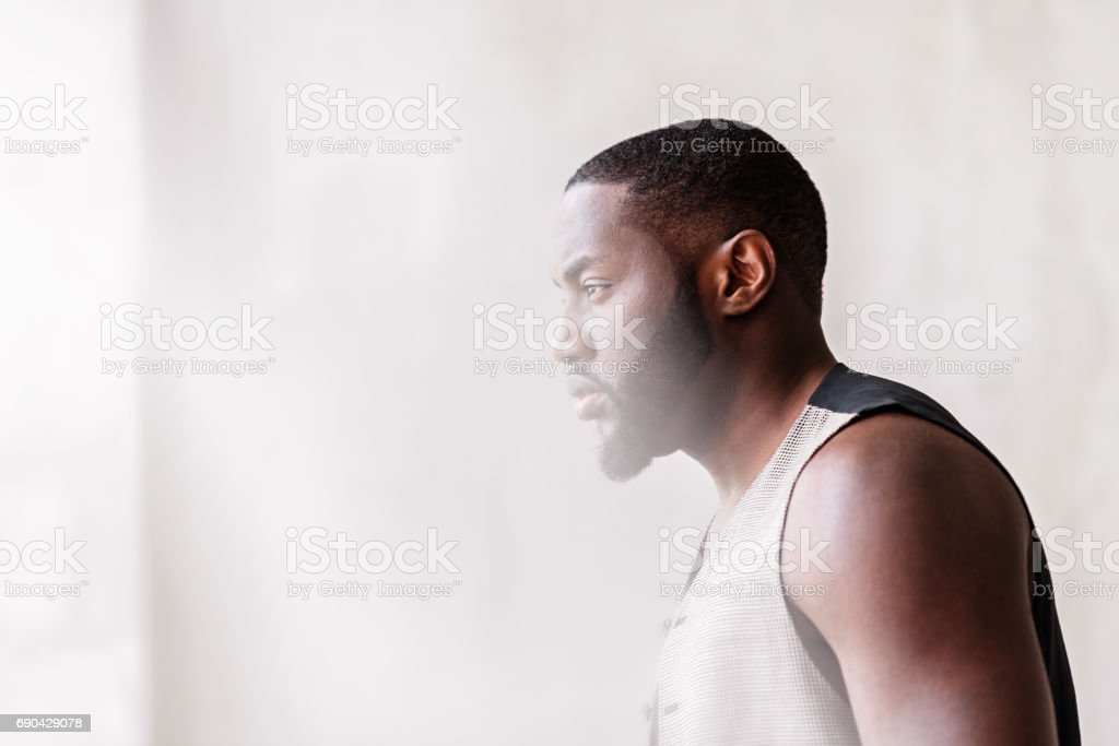 Pensive african attractive guy with beard standing by window stock photo