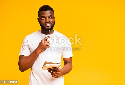 istock Pensive african guy taking notes, writing check list in notebook 1174436608