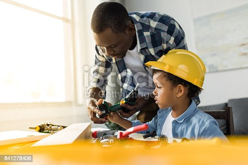 istock pensive african-american father and son doing renovation 841278406