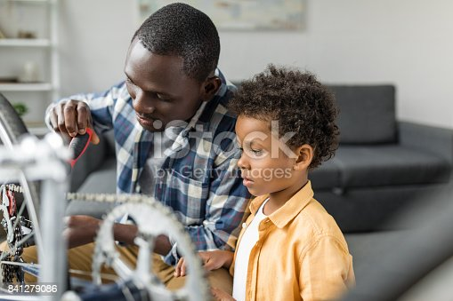 istock pensive african-american father and son repairing bicycle 841279086