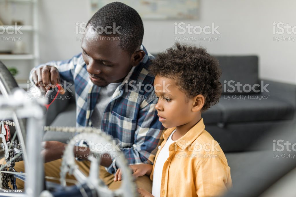 pensive african-american father and son repairing bicycle stock photo