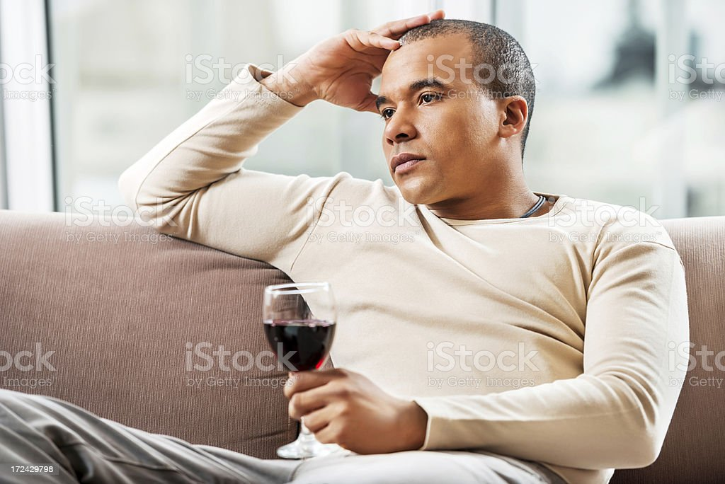 Pensive African-American man sitting at home and drinking wine. royalty-free stock photo