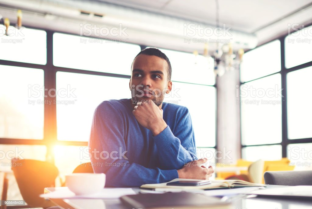 Pensive afro american businessman thinking about startup project sitting at desktop concentrated on idea.handsome serious dark skinned entrepreneur pondering on problem solution during working day stock photo