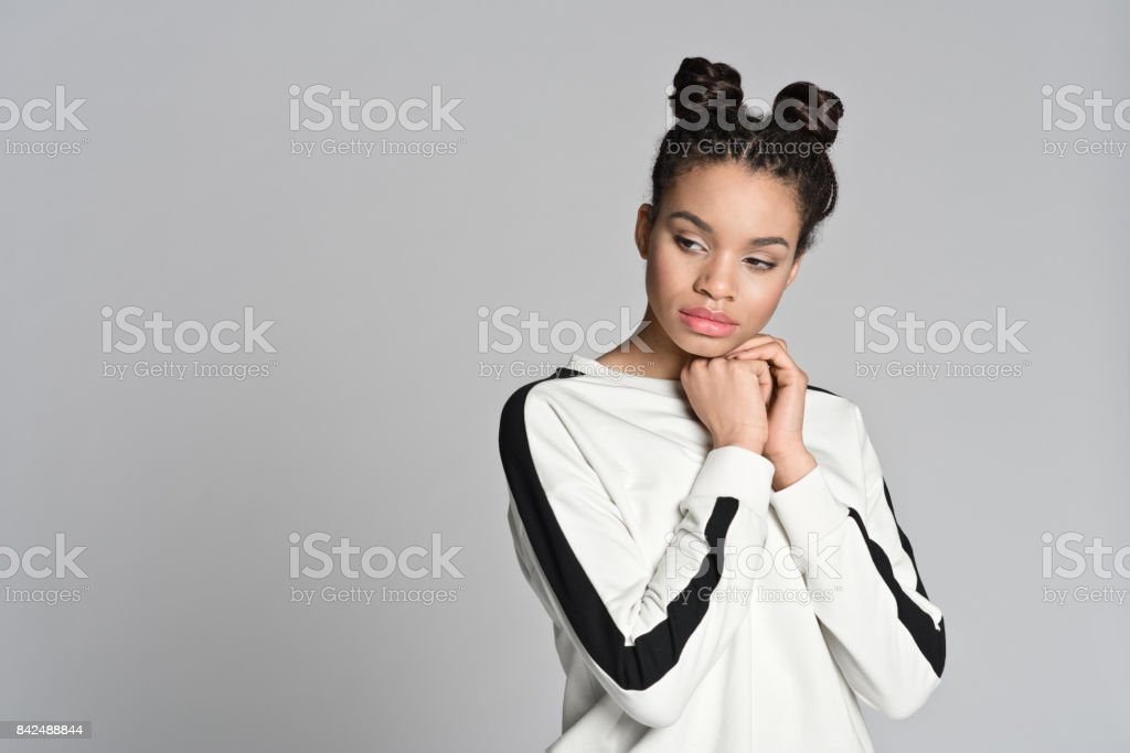 Pensive afro american cute teenager woman Studio portrait of pensive afro american cute teenage woman. Studio shot, grey background. 16-17 Years Stock Photo