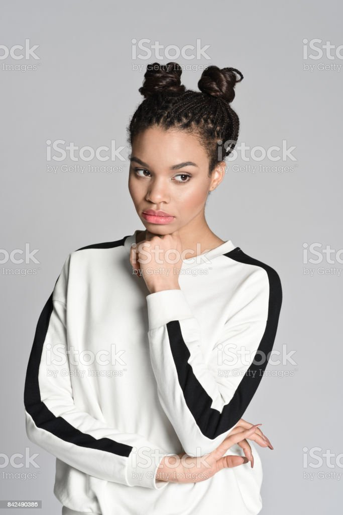 Pensive afro american cute teenager woman Studio portrait of pensive afro american teenage woman. Studio shot, grey background. 16-17 Years Stock Photo