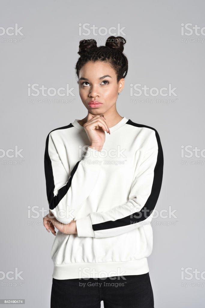 Pensive afro american cute teenager woman Studio portrait of pensive afro american teenage woman. Studio shot, grey background. 16-17 Years Stock Photo