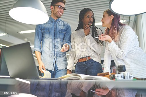905130626 istock photo Pensive afro american employee listening to explanation of colleague presenting her creative solutions for startup, students collaborating on project making decision together having discussion 905130680