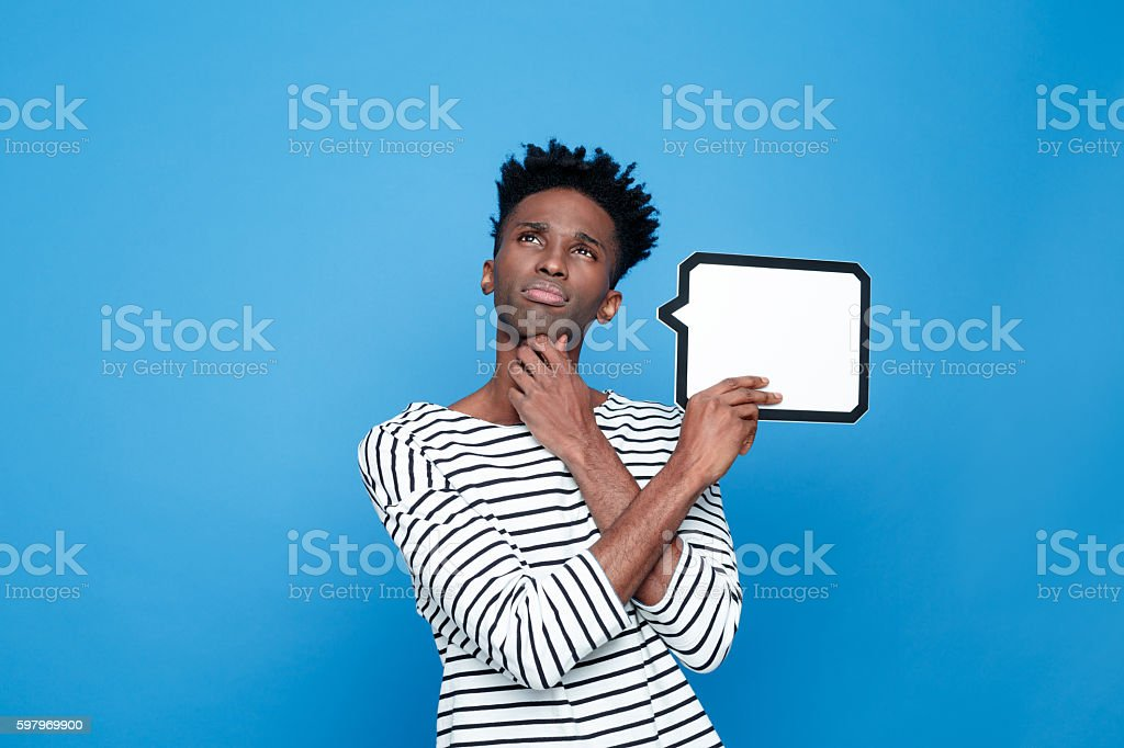 Pensive afro american guy holding speech bubble Portrait of pensive afro american young man wearing striped top, holding speech bubble in hand and looking up with hand on chin. Studio portrait, blue background. Adult Stock Photo