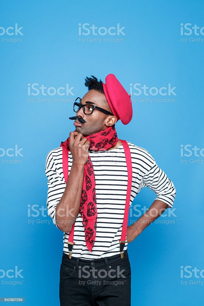 Pensive afro american guy in a french outfit Portrait of pensive afro american guy wearing striped long sleeved t-shirt, red suspenders, beret and neckscarf. Studio shot, blue background.  Adult Stock Photo