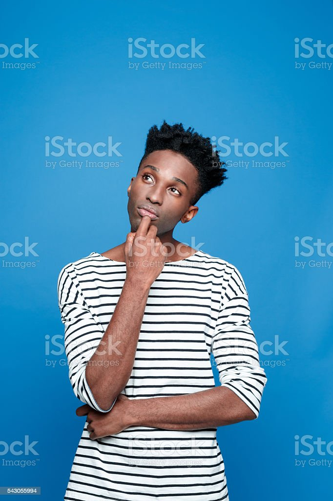 Pensive afro american guy Portrait of pensive afro american young man wearing striped top, looking up with hand on chin. Studio portrait, blue background. Adult Stock Photo