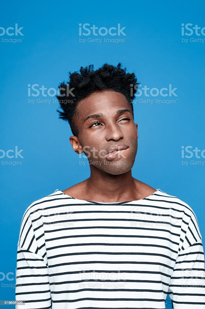 Pensive afro american guy, studio portrait against blue background Studio portrait of cute afro american young man wearing striped top with a thoughtful facial expression. Studio portrait, blue background. Adult Stock Photo