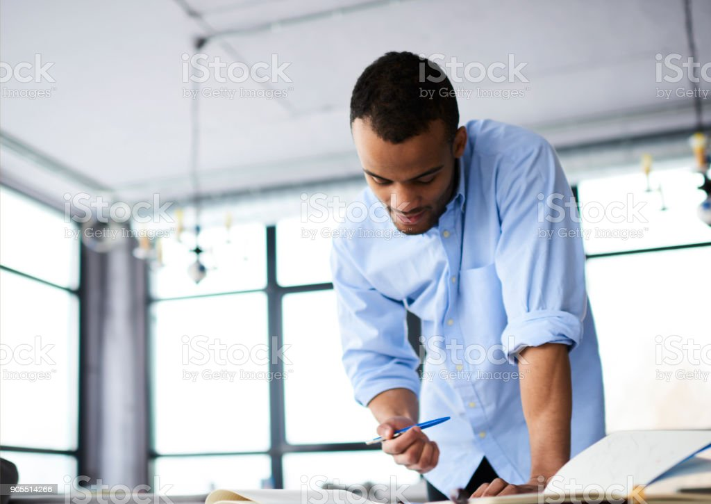 Pensive afro american male architect drafting doing plan for project in modern interior office,experienced businessman pondering on accountings and strategy for increasing incomes of company stock photo