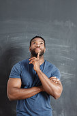 Studio portrait of pensive afro american man, standing against blackboard, looking up with finger on chin.