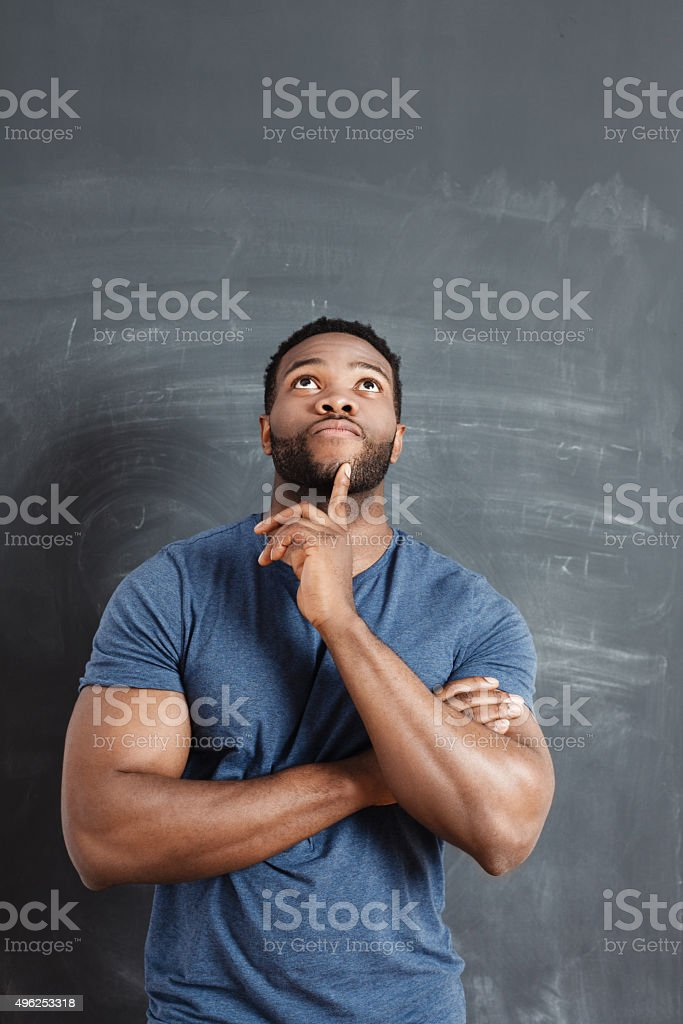 Pensive afro american man against blackboard stock photo