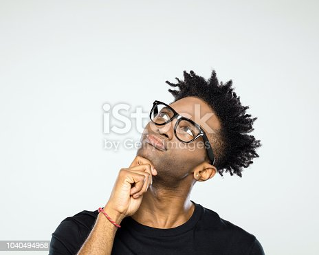 Close up portrait of pensive young afro american man wearing nerdy glasses looking up at copy space on white background