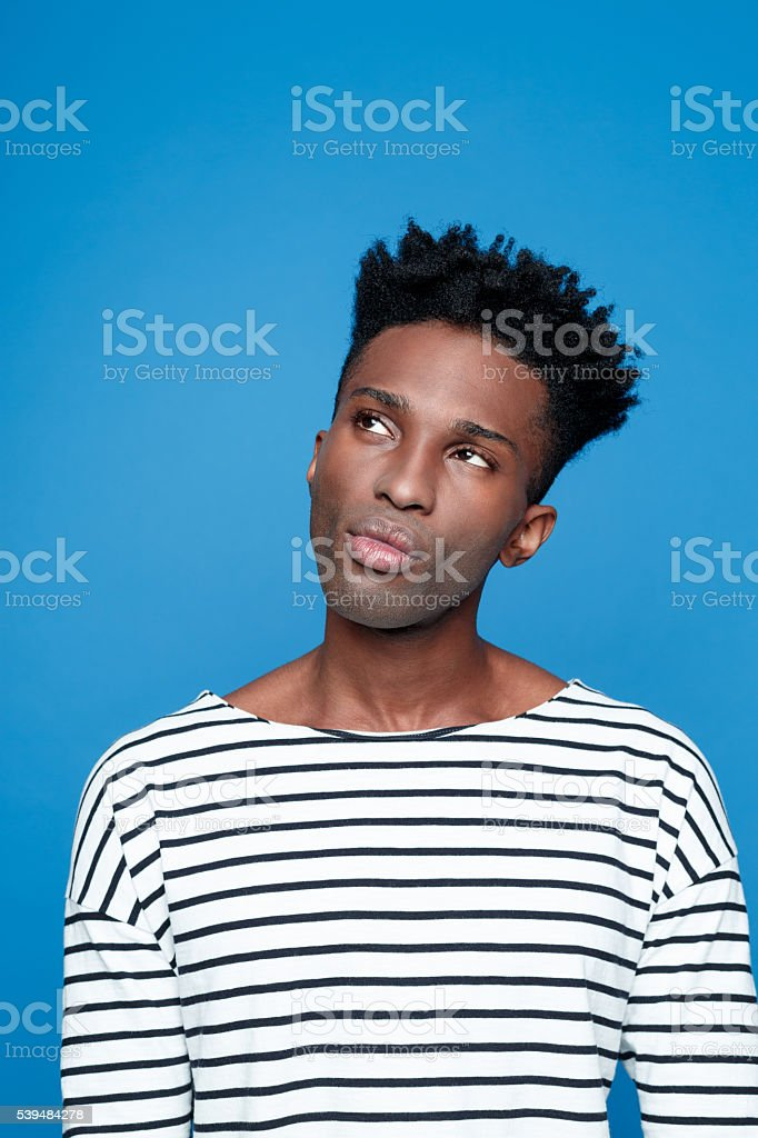 Pensive afro american young man Portrait of pensive afro american guy wearing striped long sleeved t-shirt, thinking, looking away. Studio shot, blue background.  Adult Stock Photo