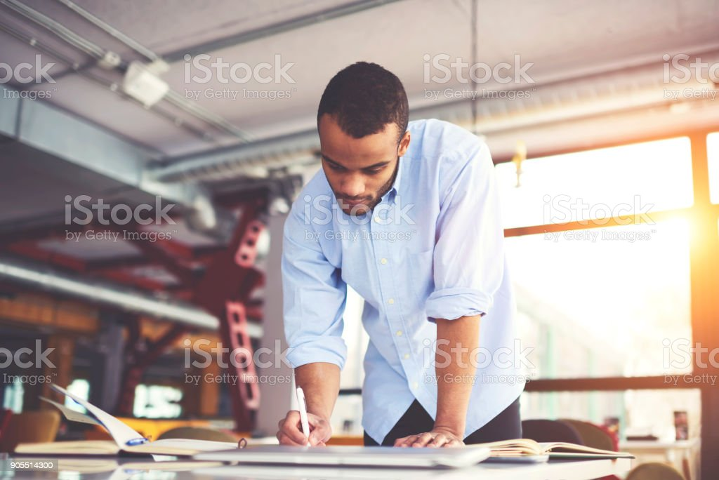Pensive afro merican architect drafting and making accountings concentrated on completing working task in office, skilled dark skinned male graphic designer in casual wear planning project stock photo