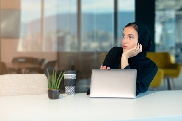 Pensive arabic businesswoman sitting at workplace in office stock photo