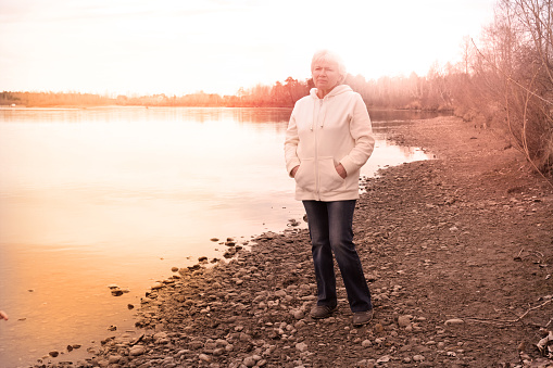Pensive attractive senior woman with  blond hair with a quiet smile as she stands on an outdoor  countryside. Haze blurred retro effect filter