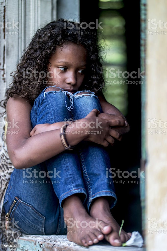 Pensive barefoot African American teenager sitting on a window f stock photo