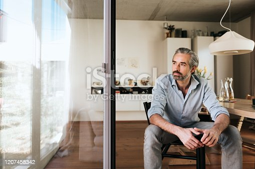 pensive  bearded business man sitting on chair looking out of the window