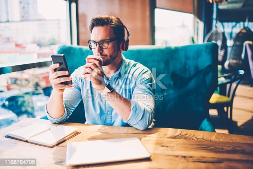 istock Pensive bearded entrepreneur in modern headphones listening music and drinking tasty coffee while reading financial news on internet website via 4G connected to smartphone sitting in coffee shop 1168764708