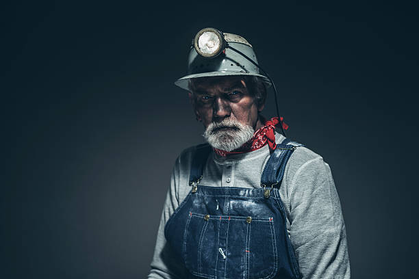 Pensive Bearded Old Gold Miner Against Gray stock photo