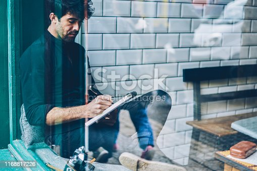 1174436608 istock photo Pensive bearded young man dressed in black shirt writing down essay in notepad resting in coffee shop interior.Skilled hipster guy noting some records in notebook sitting in coworking space 1168817226