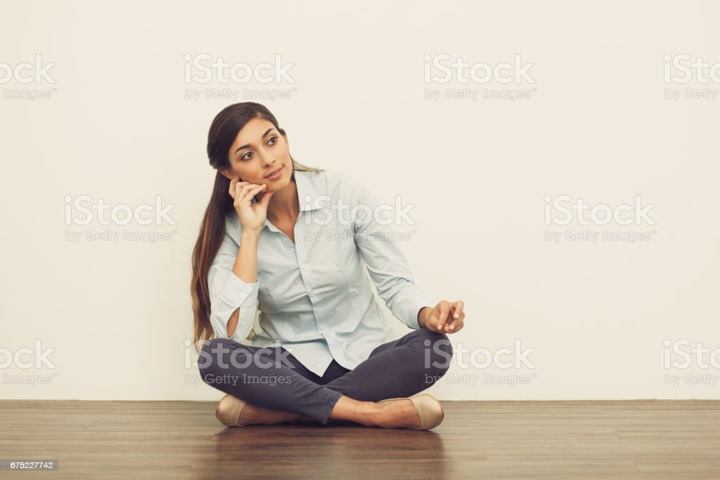 Pensive Beautiful Woman on Floor with Crossed Legs royalty-free stock photo