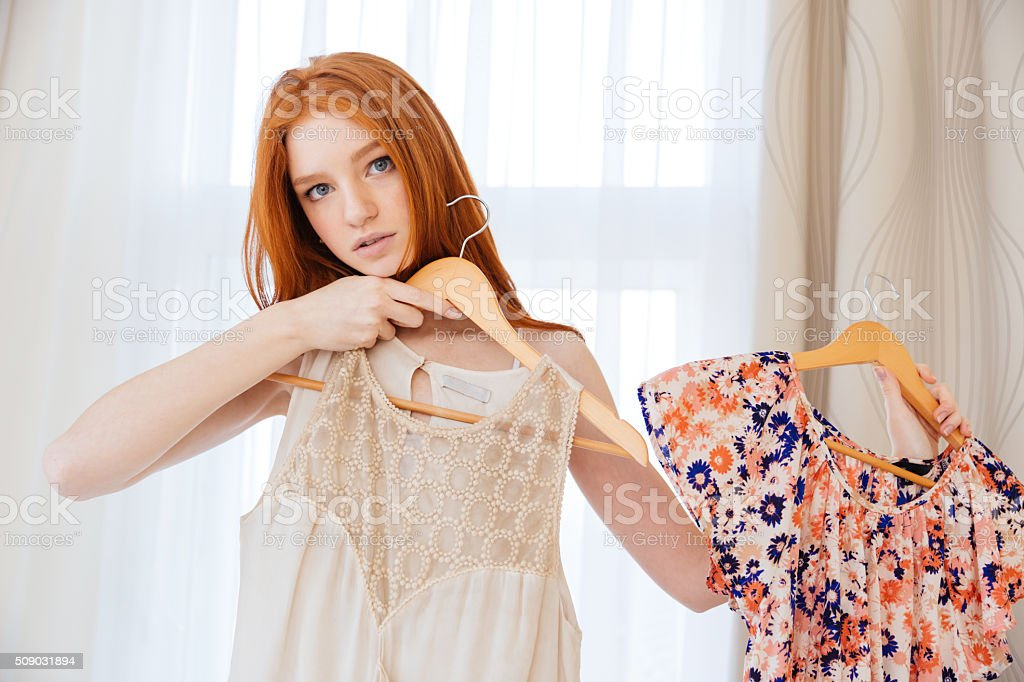 Pensive beautiful young woman desiding what to wear stock photo