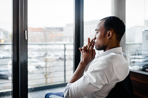 Pensativo negro hombre de negocios mirando a - foto de stock