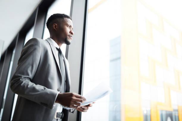 Umfassender schwarzer Unternehmer mit Papieren in der Nähe des Fensters – Foto