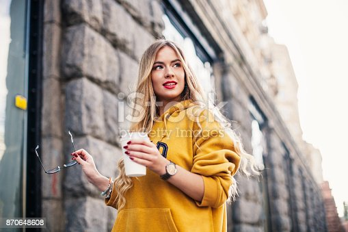 870648602 istock photo Pensive blond woman posing on modern streets, drinking coffee or cappuccino Street fashion concept, young woman wearing boyfrend jeans,glasses, white sneakers bright yellow sweetshot 870648608