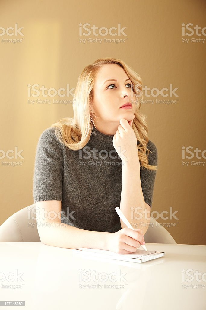 Pensive Blonde Woman Writing a To Do list stock photo