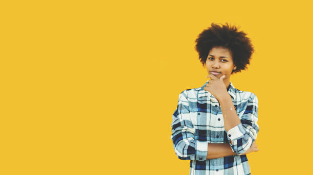 Pensive brazilian girl on isolated yellow background stock photo