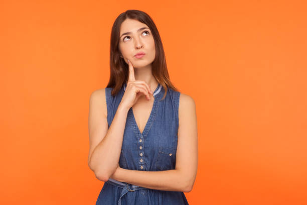 Pensive brunette woman in denim dress looking up with thoughtful doubtful expression stock photo