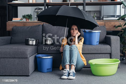 Pensive brunette girl sitting on floor with umbrella